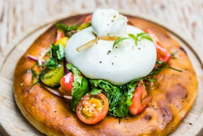 Burrata koos kirju kirsstomati salati, punase sibula, värskete ürtide ja oliivõli kastmega ning soe Foccacia leib
