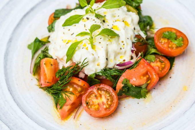 Straccitella koos kirju kirsstomati salati, punase sibula, värskete ürtide ja oliivõli kastmega